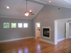 Empty-Bedroom-Use-Red-Oak-Flooring-with-Modern-Ceiling-Fan-and-Ceiling-Lamp-with-Grey-Painted-Wall-and-Mounted-Fireplace